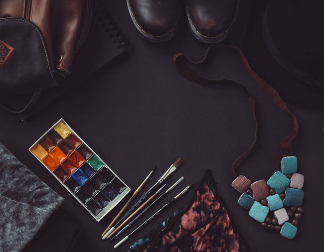 High Angle View Of Watercolor Paints And Paintbrush By Necklace