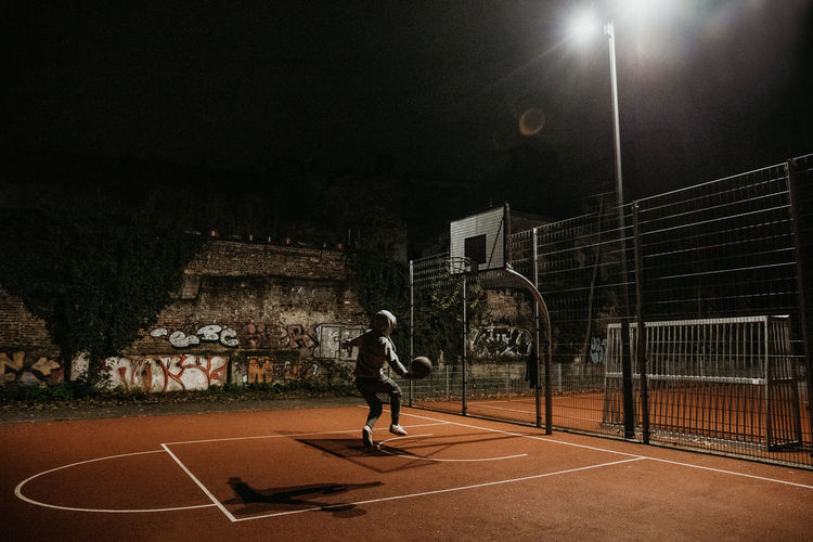 Man playing with ball in background at night