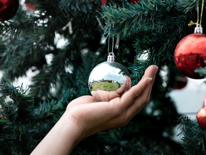 Close up of hand holding on christmas baubles, balls on christmas tree branch.  merry christmas.