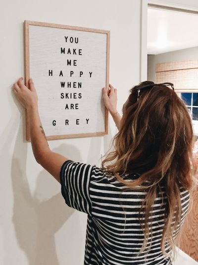 Hanging Holding Up Message Board Tune Lyrics Saying One Person Text Indoors  Women Hairstyle Hair Real People Standing Holding Waist Up Long Hair Adult Lifestyles Board