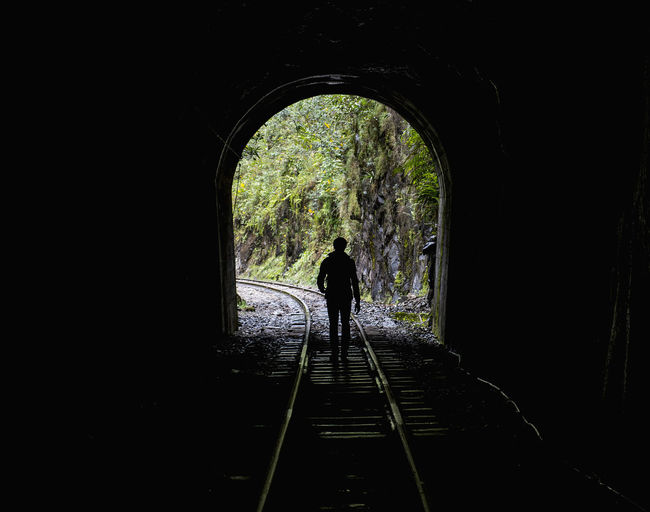 Rear view of silhouette person standing in tunnel