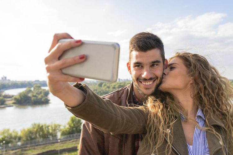 Happy young couple taking selfie photos near the river Camera Communication Couple - Relationship Hair Happiness Mobile Phone Outdoors Photography Themes Portable Information Device Portrait Positive Emotion Selfie Smart Phone Smiling Technology Togetherness Two People Wireless Technology Women Young Adult Young Men Young Women
