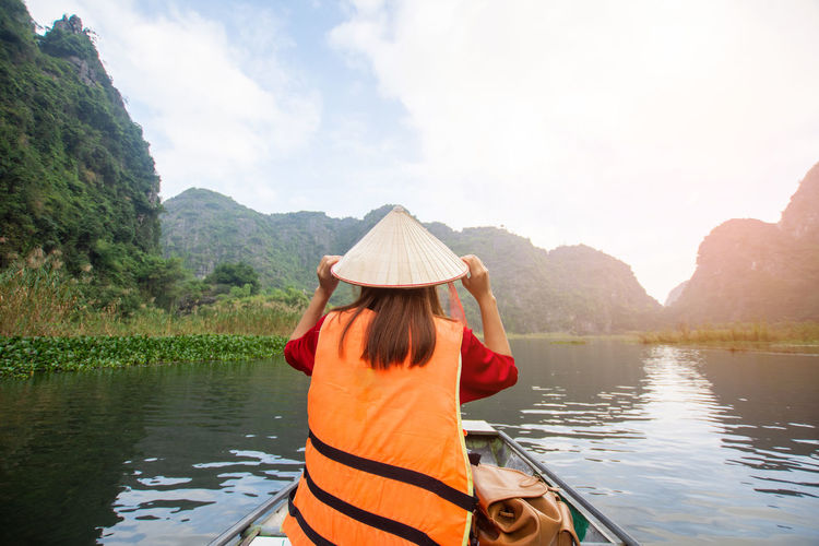 Tam Coc, Vietnam Water Sky One Person Lake Mountain Rear View Real People Nature Scenics - Nature Beauty In Nature Day Lifestyles Leisure Activity Adult Nautical Vessel Non-urban Scene Cloud - Sky Women Mountain Range Outdoors Human Arm Hairstyle Arms Raised Tam Coc Vietnam Travel