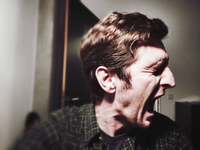 Close-Up Of Mid Adult Man Screaming At Home