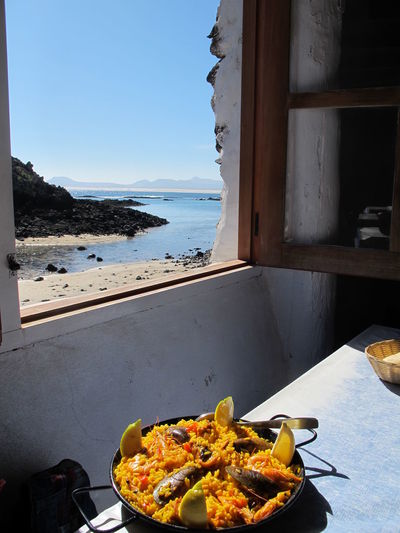 Close-Up Of A Pot Of Paella With Seascape In Background