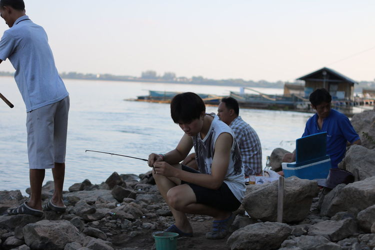 Mekong River NongKhai,ThaiLand Beach Casual Clothing Country Life Countryside Day Friendship Full Length Holding Leisure Activity Lifestyles Men Nature Outdoors Real People Rock - Object Sea Sitting Sky Standing Still Life Togetherness Water Young Adult