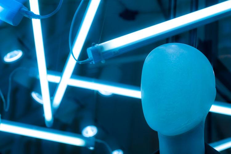 Close-up of mannequin against fluorescent lights in darkroom