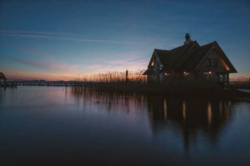 Scenic view of lake by building against sky during sunset