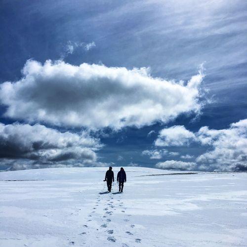 Men on snowcapped landscape against sky