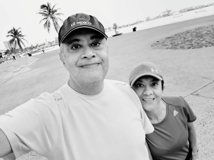 Portrait of smiling couple standing on promenade