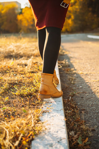 Happy fall, hello autumn, fall season. female legs in yellow boots walking along the curb with fall