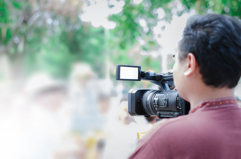 Rear view of man operating home video camera outdoors