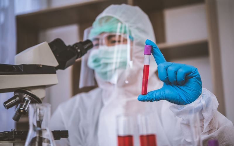 Close-up of doctor examining over microscope