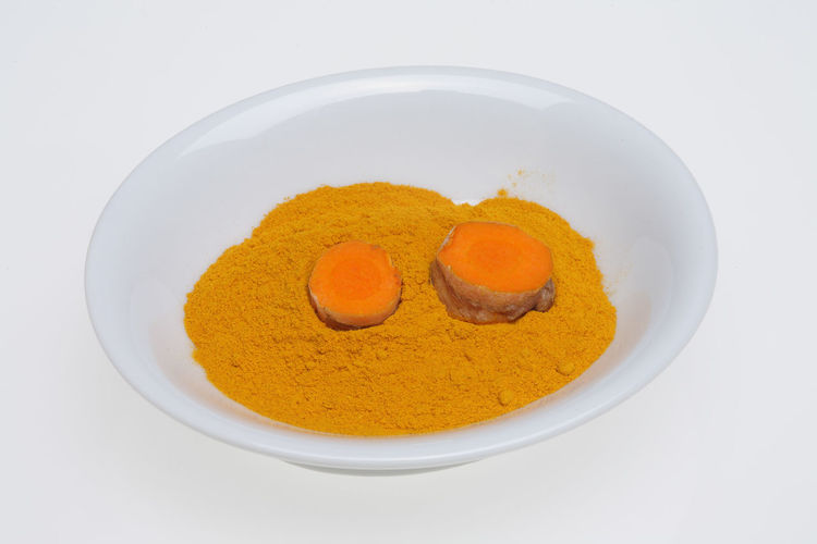 Turmeric, Curcuma longa, a rhizomatous herbaceous perennial plant as spice and medicinal herb Curcuma Food Herb Medicinal Plant Spices Studio Shot Turmeric  White Background