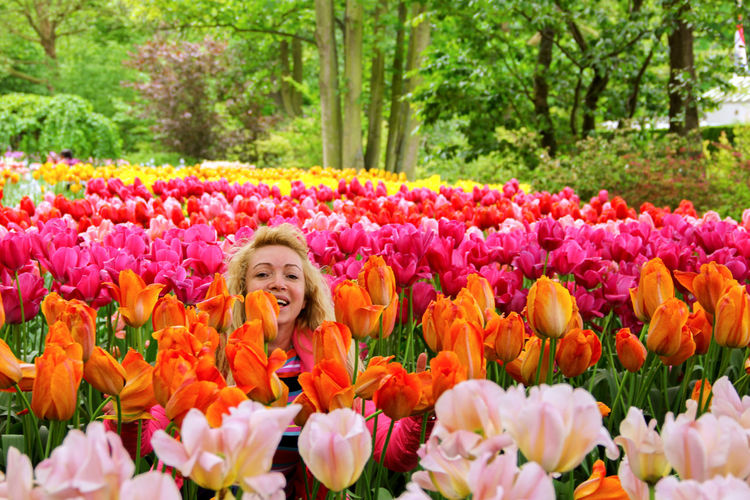Young woman on a glade among the tulips Beauty In Nature Blooming Field Flower Girl Glade Growth Happy Lifestyles Meadow Meadow Flowers Multi Colored Nature Person Pink Color Smile Smiling Tulip Woman