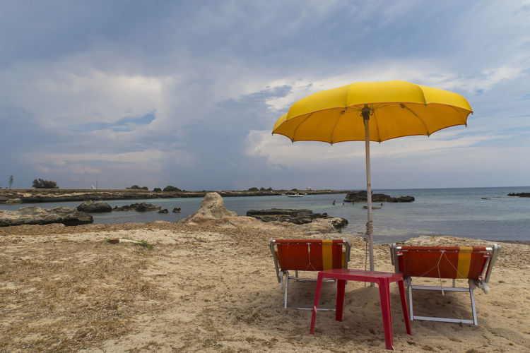 Deck chairs and tables on beach against sky