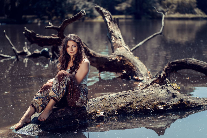 Young woman sitting on a big tree trunk in a lake Beautiful People Beautiful Woman Beauty Beauty In Nature Brown Hair Fantasy Fashion Fashion Model Females Long Hair Looking At Camera Nature One Person One Woman Only One Young Woman Only Only Women Outdoors Portrait Real People Sitting Water Women Young Adult