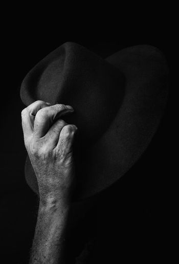 Close-Up Of Man Holding Hat Against Black Background