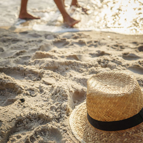High Angle View Of Straw Hat On Shore Of Beach