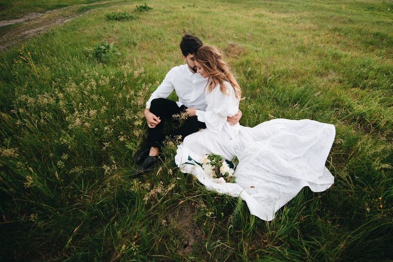 Bride And Bridegroom Sitting On Grassy Field