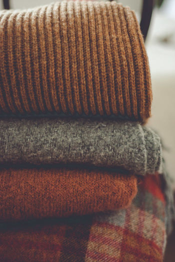 Close-up of sweaters stacked at home