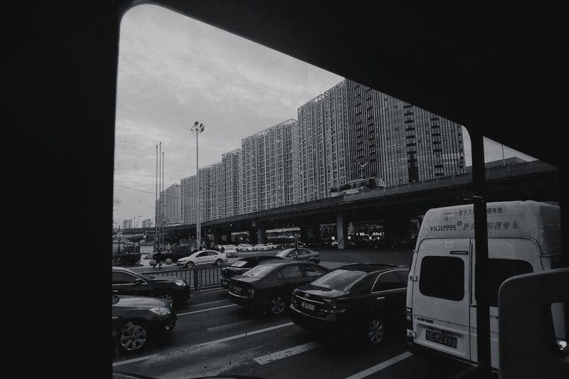 Traffic on road by buildings against sky
