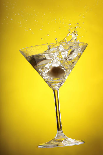 Close-up of wine in glass against yellow background