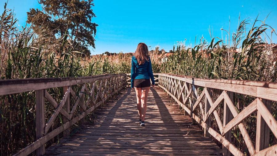 Rear view of woman on footbridge