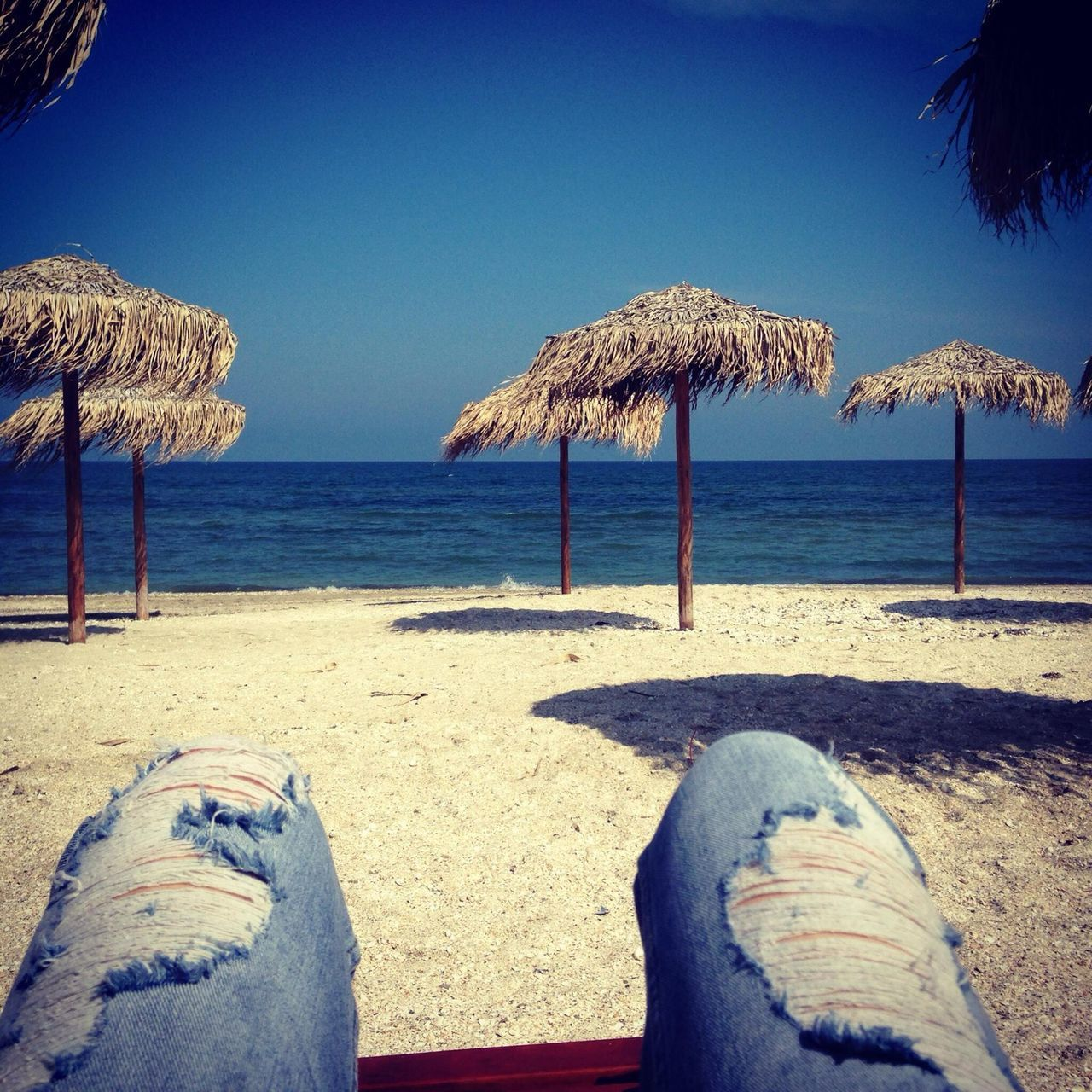 beach, sea, shore, water, day, sand, thatched roof, nature, outdoors, horizon over water, beauty in nature, tranquility, tranquil scene, blue, human leg, vacations, sunlight, scenics, clear sky, low section, one person, sky, people