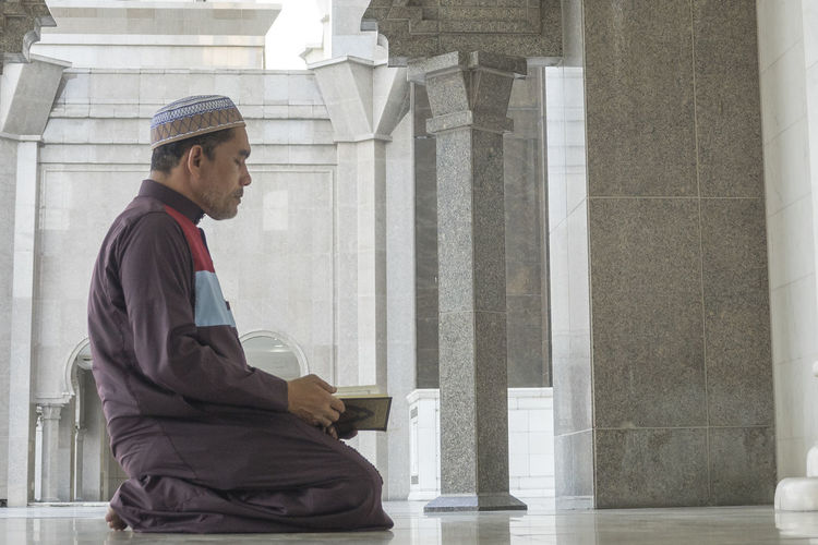 Side View Of Mature Man Reading Koran While Kneeling At Mosque