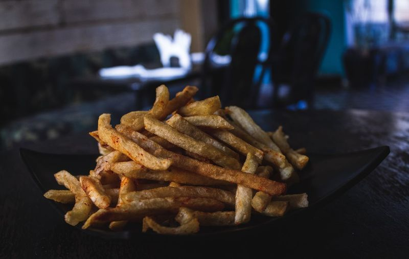 Fried Ready-to-eat French Fries Prepared Potato Fast Food Unhealthy Eating Potato Food Food And Drink Freshness Still Life Deep Fried  Snack Table Close-up Focus On Foreground No People Indoors  Serving Size Fast Food French Fries French Food Comfort Food Temptation