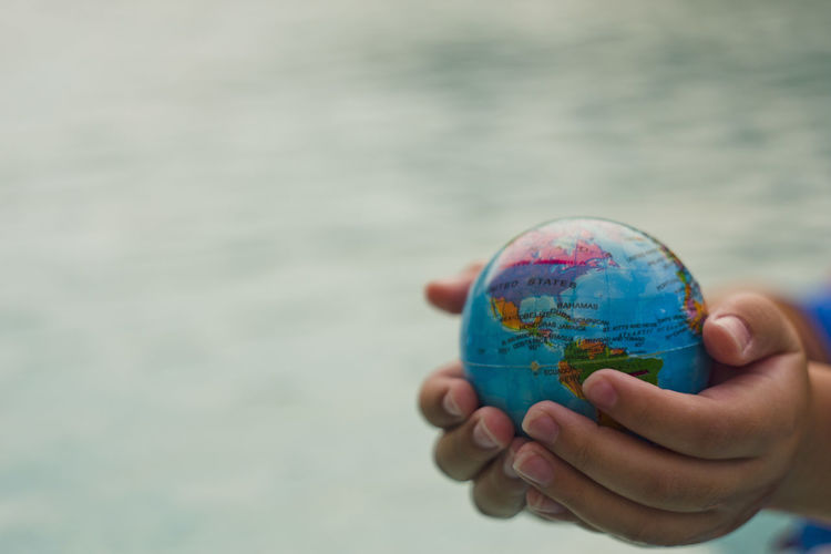 Above close up looking down on hand holding the world over water Atlantic Ocean Hand Holding Hands Map Plant Power USA America Canada Cat Continent Ecology Energy Ocean Planet Protection South America Sustainability Sustainable Sustainable Resources Water World