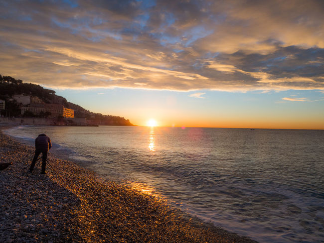Beach Beauty In Nature Cloud - Sky Côte D'Azur France Nature Orange Color Outdoors Person Rear View Remote Scenics Sea Shore Sky Solitude Summer Sun Sunset Tranquil Scene Tranquility Vacations Water Wave