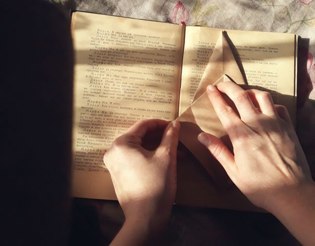 Midsection of woman reading book on paper