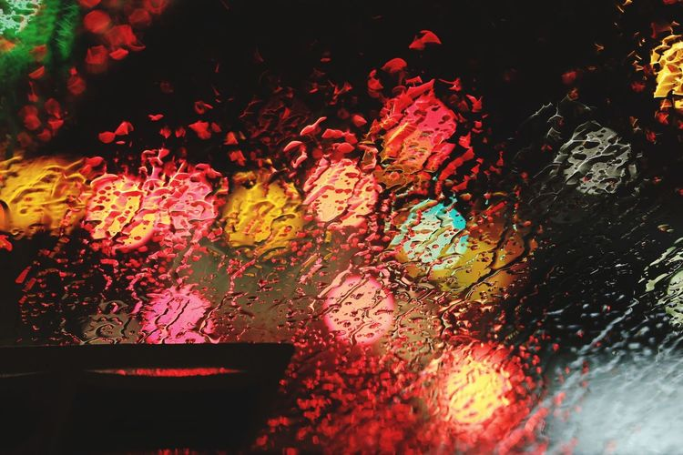 Outdoors No People Red Raindrops Rainy Night Rain drops on the car front mirror with the reflection of lights.