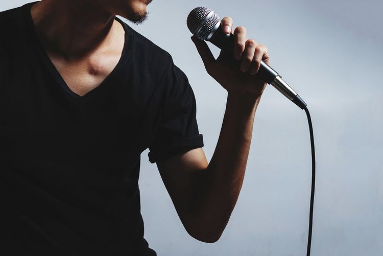 Midsection Of Man Holding Microphone While Singing Against Gray Background