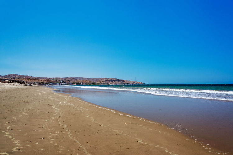 View looking down the beach in Mancora, Peru Beach Coastline Destination Horizon Over Water Idyllic Mancora Mancorabeach Nature Ocean Pacific Outdoors Peru Rural Sand Sandy Scenics Sea Shore Sunny Tourism Town Tranquil Scene Travel Vacations Village Water
