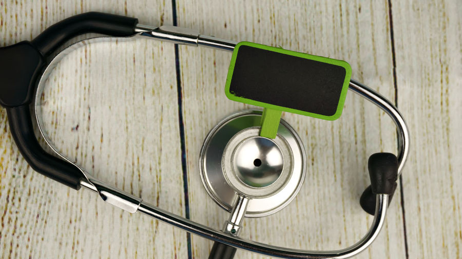 Stethoscope With Blank Board On Wooden Table
