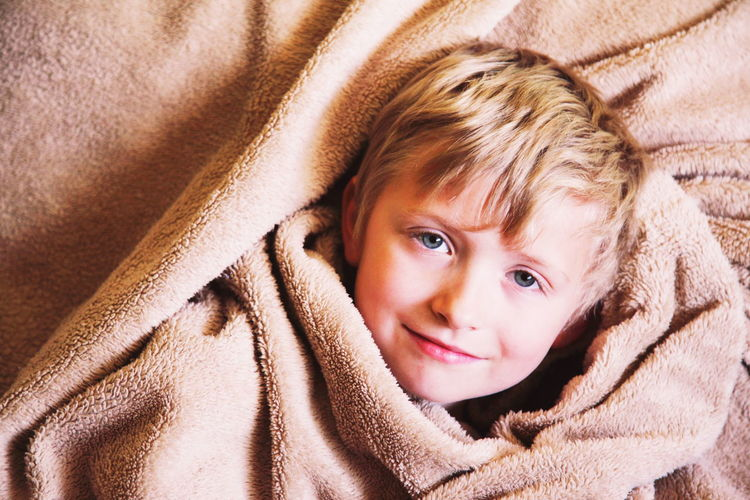 Child in Blanket Boy Child Childhood Comfy  Cute Happiness Headshot High Angle View Indoors  Innocence Leisure Activity Lifestyles Looking At Camera Peaceful Person Portrait Real People Resting Smiling