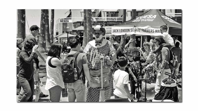 Hanging Out At Jack London Square 2 Port Of Oakland, Ca. Jack London Square Bnw_friday_eyeemchallenge Bnw_street Bnw_streetphotography Balloon Man Clown Bubbles! Urban Photography Farmers Market Tent People Watching Kids Adults Umbrellas Monochrome_Photography Monochrome Black & White Black & White Photography Black And White Black And White Collection  Urban Photography Palm Tree Trunks