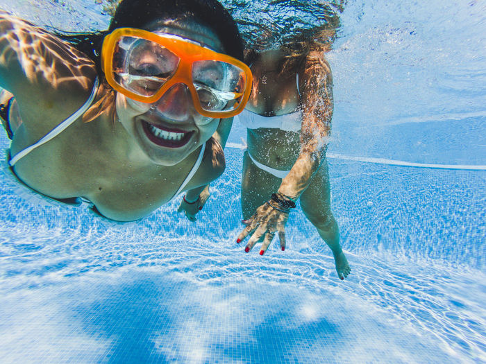 Portrait of happy woman with female friend swimming in pool