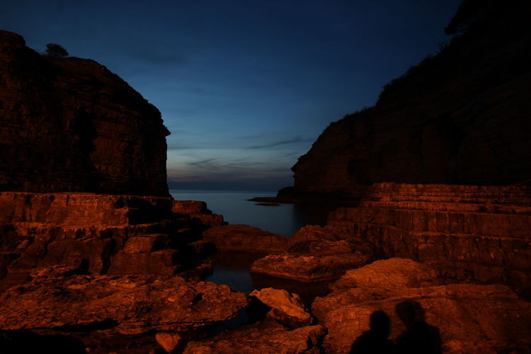 Rock formations by sea against sky during sunset