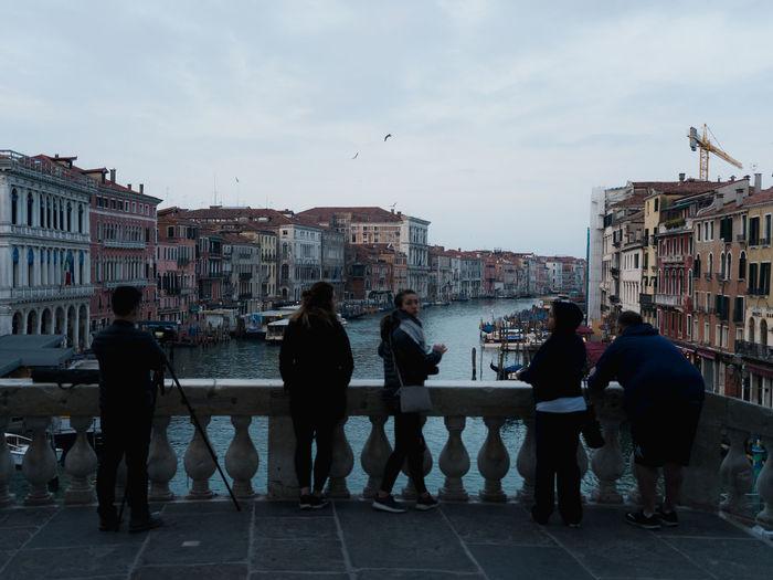 People walking by buildings in city against sky