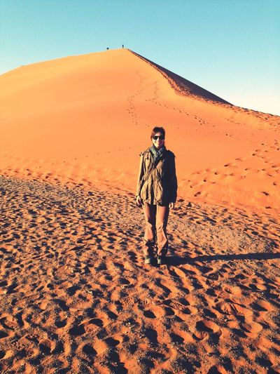 Full length of man on sand dune in desert against sky