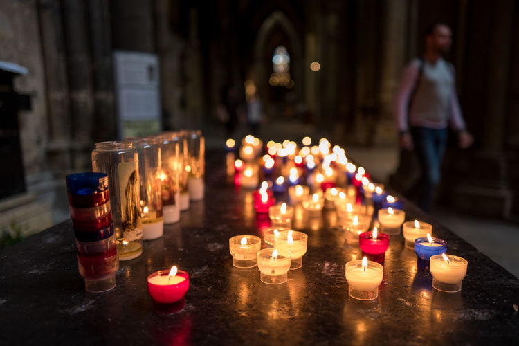 Lit Tea Light Candles On Table In Metz Cathedral