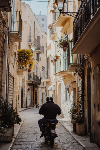 Man drives through small streets of Bari, Italy Bari Driving Man Moped Plants Scooter Transportation Travel Alleyway Architecture Balconies Building Exterior Built Structure City Day Europe Italy One Person Outdoors Rear View Riding Small Street Streetphotography The Way Forward Vintage Photo