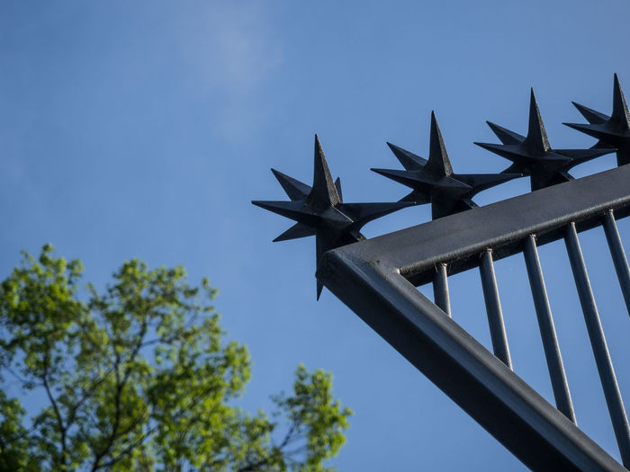 Low Angle View Of Spiked Stars On Metal Fence Against Clear Blue Sky