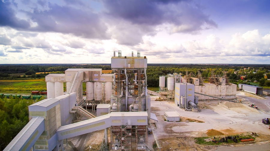 Overview of the limestone factory where there are lots of stones inside and some trucks and machineries moving inside Cloud - Sky Sky Architecture Nature Building Exterior Built Structure Day Industry High Angle View No People Landscape Outdoors Environment Factory Sunlight Plant Horizon Land Fuel And Power Generation Horizon Over Land Aerial View Limestone Quarry Stone Material Mining Object Industry Construction Rock Mineral Earth Gravel Equipment Machinery