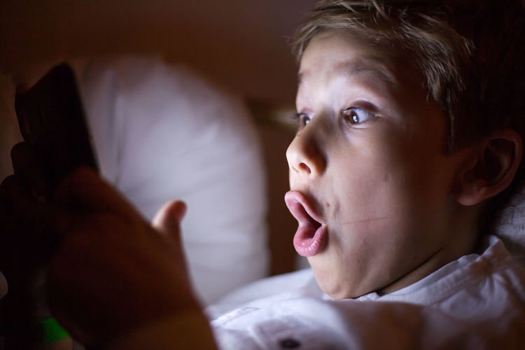 Shocked boy using smart phone in darkroom