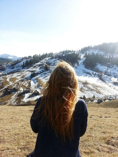 Rear View Of Woman Standing In Front Of Snowcapped Mountains